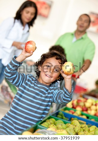 Family at the supermarket shopping for some fruits - stock photo