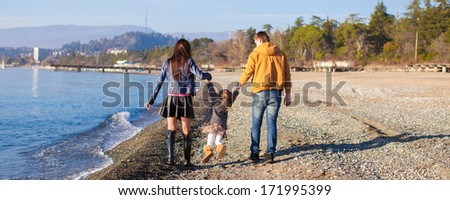 Family at winter beach during the warm day - stock photo