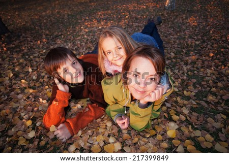 Family autumn portrait - laying on the ground among yellow leaves - stock photo