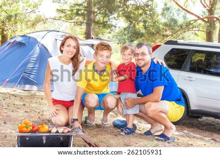 Family barbecue vacation. Happy family has picnic (bbq). Healthy food (meal) on flaming hot. Relaxing mother, father and sons near tent, car and having fun in summer day. Travel, adventure concept. - stock photo