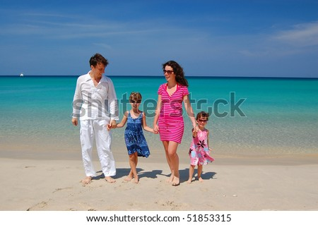Family beach vacation. Parents with two children having a walk on the beach - stock photo