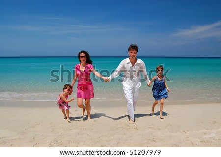 Family beach vacation. Parents with two kids having fun on the beach - stock photo