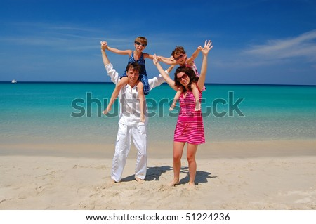 Family beach vacation. Parents with two kids having fun on the beautiful beach - stock photo