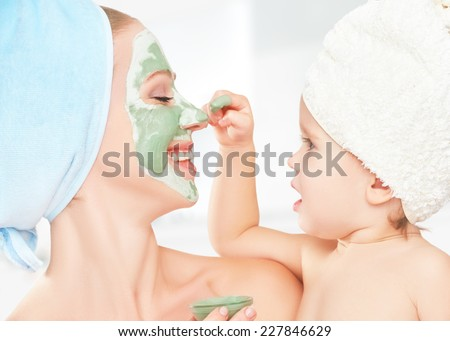 family beauty treatment in the bathroom. mother and daughter baby girl make a mask for a face skin - stock photo