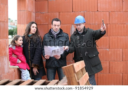 Family being shown around construction site - stock photo