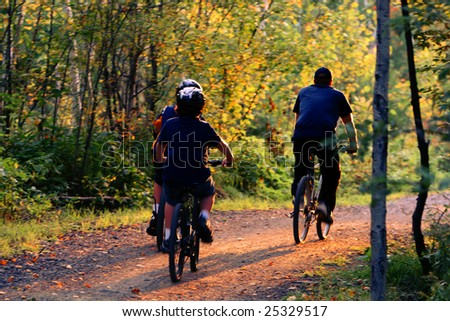 family bike riding in the woods - stock photo