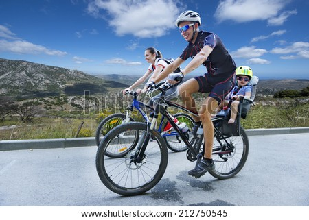 Family bike trip in the mountains - stock photo
