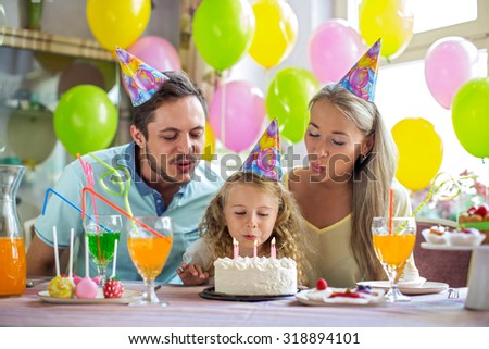 Family blows out the candles on the cake - stock photo