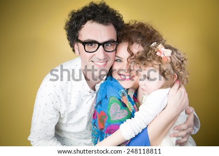 Family bonding concept.Happy family,mother and father with their adorable baby girl.Loving husband hugging his wife and daughter.Family with curly hair gene - stock photo