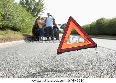 Family Broken Down On Country Road With Hazard Warning Sign In Foreground - stock photo