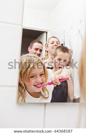 Family brushing teeths in the bathroom - stock photo