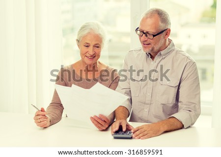 family, business, savings, age and people concept - smiling senior couple with papers and calculator at home - stock photo