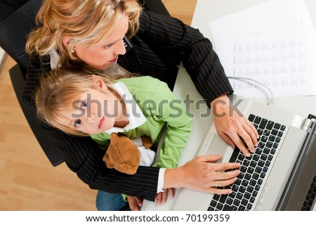 Family Business - telecommuter Businesswoman and mother is working in the internet while her daughter looks to the viewer - stock photo