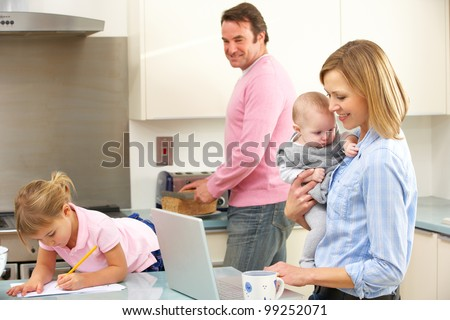 Family busy together in kitchen - stock photo