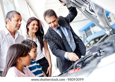 Family buying a car and looking at the engine - stock photo