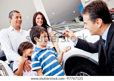 Family buying a new car and getting the keys from salesman - stock photo
