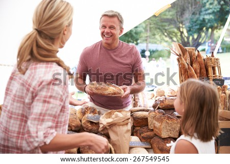 Family Buying Bread From Bakery Stall At Farmers Market - stock photo