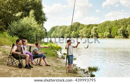 family camping and fishing, river and forest, summer season - stock photo