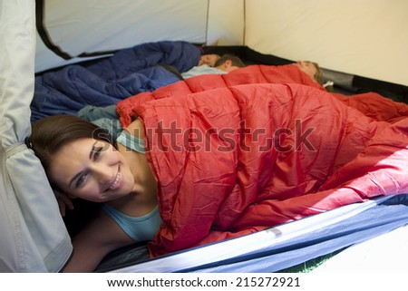 Family camping in tent, children (8-10) sleeping in background, focus on mother resting in sleeping bag in foreground, smiling, portrait - stock photo