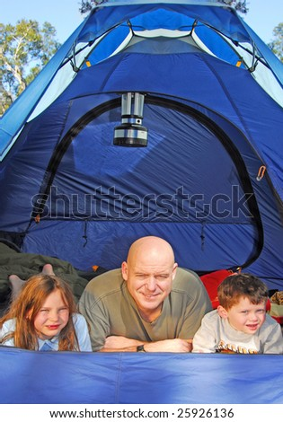 family camping in tent in woods - stock photo