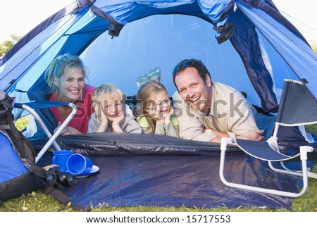 Family camping in tent smiling - stock photo