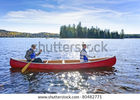 Family canoeing on sunny Lake of Two Rivers, Ontario, Canada - stock photo