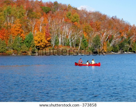Family canoes in Meech lake in gatineau park surrounded by spectacular fall colors