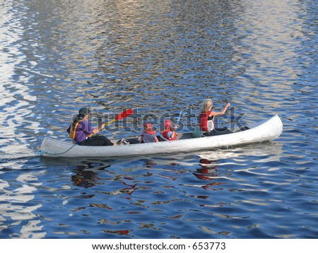 Family canooing at a river. - stock photo