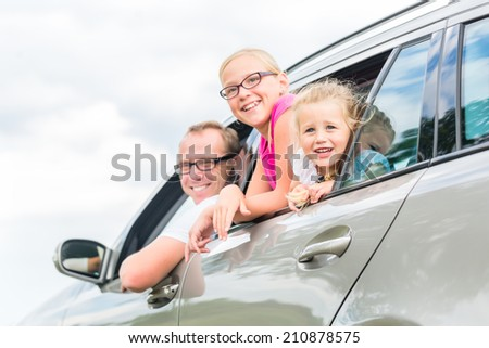 Family car - Father driving with daughters in auto - stock photo