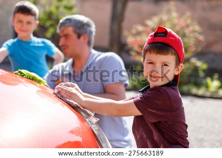 Family car wash day, little boy cleaning spotlight, father and brother in background out of focus - stock photo