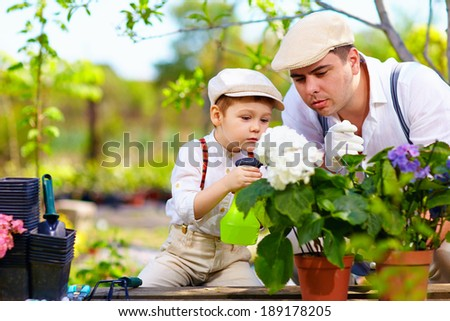 family cares for plants in spring garden - stock photo