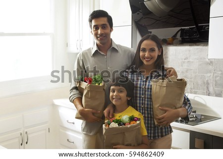 Family carrying bags of groceries in kitchen