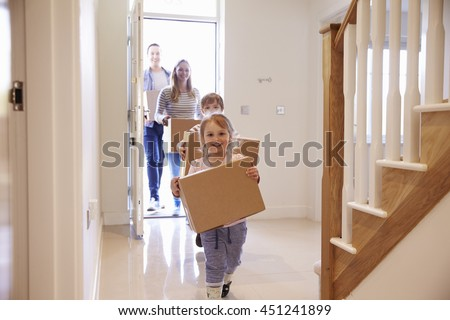 Family Carrying Boxes Into New Home On Moving Day - stock photo