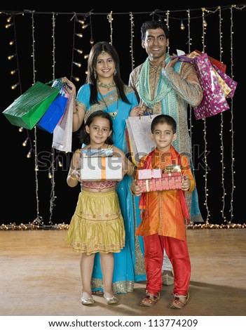 Family carrying shopping bags and gifts for Diwali