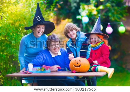 Family carving pumpkin at Halloween. Dressed up child trick or treating. Kids and parents trick or treat. Child in witch costume playing in autumn park. Toddler kid with jack-o-lantern.  - stock photo