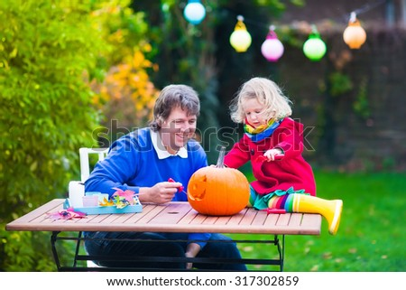 Family carving pumpkin at Halloween. Dressed up child trick or treating. Kids and parents trick or treat. Child in witch costume playing in autumn park. Toddler kid with jack-o-lantern - stock photo