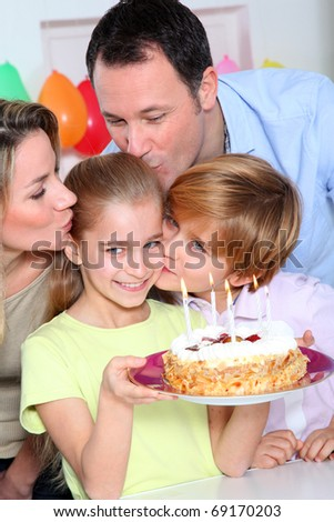 Family celebrating child's birthday - stock photo