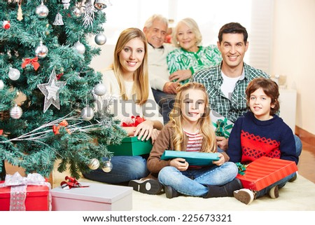 Family celebrating christmas with three generations under tree with gifts - stock photo