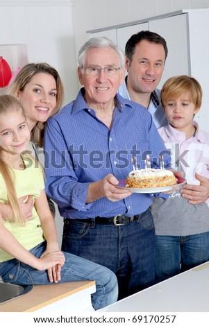 Family celebrating grandfather's birthday - stock photo