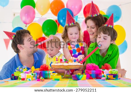 Family celebrating kids birthday. Parents and children celebrate together. Child party with balloon decoration, cake, candles and present boxes. Celebration for baby boy, toddler girl and school kid - stock photo