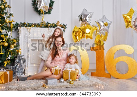 Family celebration of the New Year 2016. The mother and two daughters near a Christmas tree. Giving gifts. Holiday and fun. - stock photo