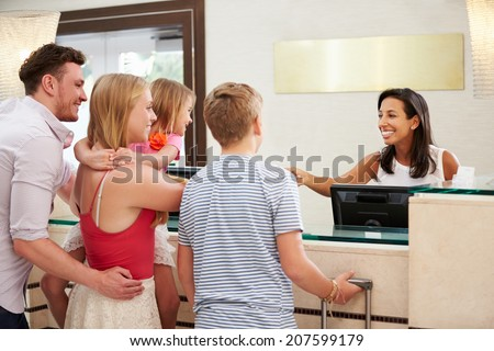 Family Checking In At Hotel Reception - stock photo