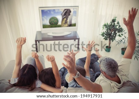 Family cheering and watchin tv at home in the living room - stock photo