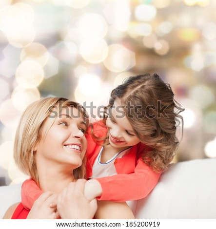family, child and happiness concept - hugging mother and daughter