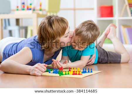 Family child and mom playing board game at home on the floor at home - stock photo