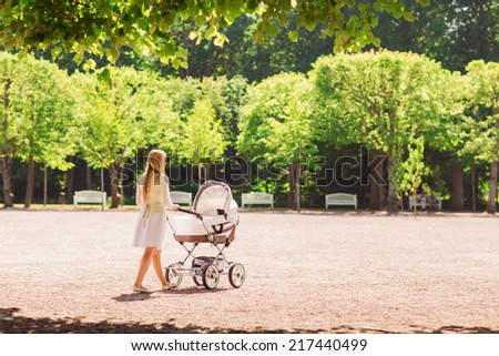 family, child and parenthood concept - happy mother walking with baby stroller in park from back - stock photo