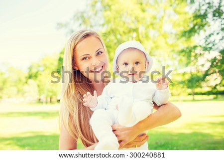family, child and parenthood concept - happy mother with little baby in park - stock photo