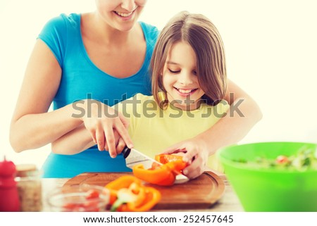 family, child, cooking and home concept - smiling little girl with mother chopping pepper in the kitchen - stock photo