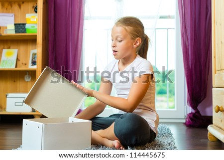 Family - child or teenager open a gift or box at home in the living room - stock photo