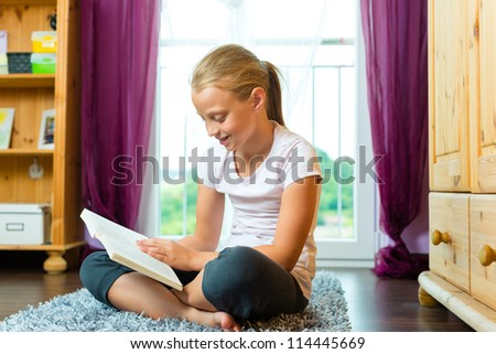 Family - child or teenager reading a book at home in the living room - stock photo